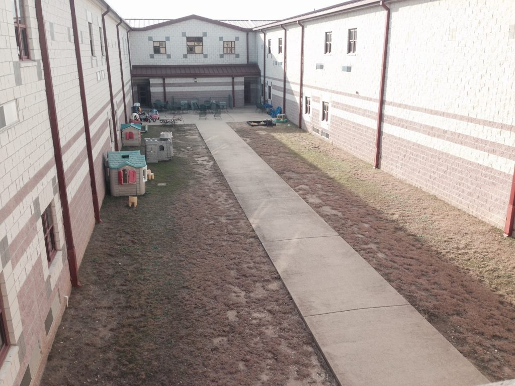 BEFORE image of courtyard. Barren and boring.